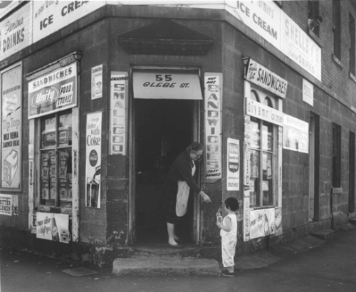 'Here is your change'. Corner shop, 55 Glebe St, Glebe, Sydney, 1964 (image: Raymond de Berquelle, National Library of Australia). The storekeeper handing over the change in 1964 is probably Edna Taylor.