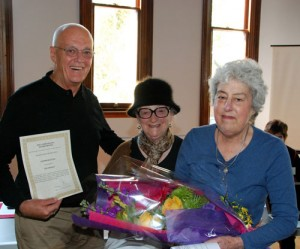Norma Hawkins (centre)  who proposed Jan's Commendation presented her with a bunch of flowers at the AGM. President John Gray (left) holds a copy of the Commendation.